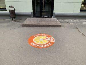 Реклама на асфальте магазина Апельсин