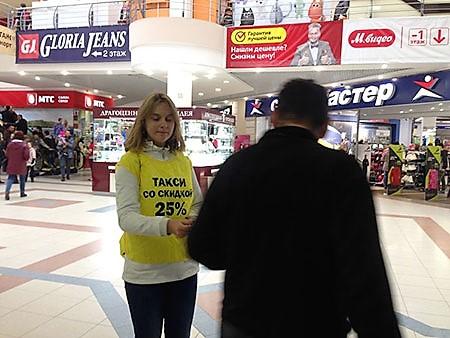 Промоутер в ТРК Столица раздает карты такси
